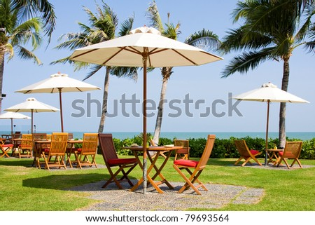 Terrace of a restaurant with  white sun shades on a beautiful caribbean beach - stock photo