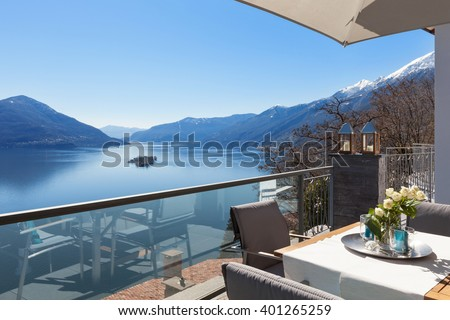 Terrace of house with dining table and lake view  - stock photo