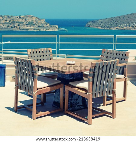 Terrace seaview with outdoor wood chairs and table in a luxury resort(Crete, Greece). instagram effect, square image - stock photo