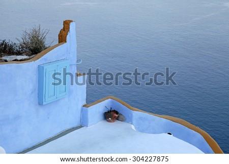 Terrace with colorful walls above Aegean sea, Oia village, island of Santorini, Greece in twilight. Selective focus - stock photo