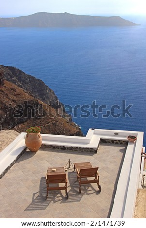Terrace with deck chairs. View to the caldera in Santorini island, Greece - stock photo