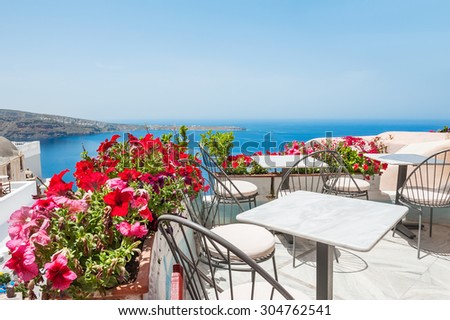 Terrace with flowers. Oia, Santorini island, Greece. Beautiful summer landscape with sea view. Selective focus - stock photo