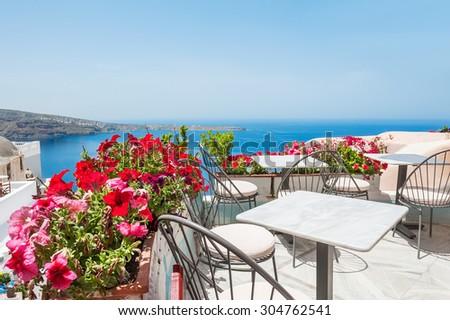 Terrace with flowers. Oia, Santorini island, Greece. Beautiful summer landscape with sea view. Selective focus - stock photo
