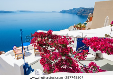 Terrace with relax area and red flowers. White architecture on Santorini island, Greece. Beautiful landscape with sea view. - stock photo
