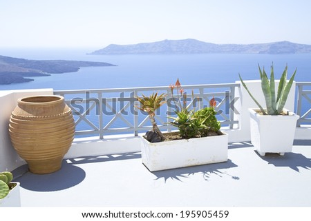 Terrace with the Mediterranean flowers on Santorini island - stock photo