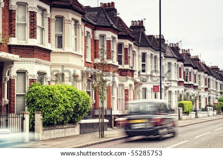"Terraced Houses and blured ""Black Cab""in  Clapham ,London. (Long exposure) - stock photo"