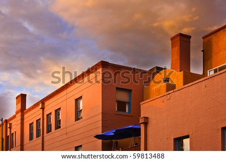 Terracotta brick and adobe roof tops at sunset. - stock photo