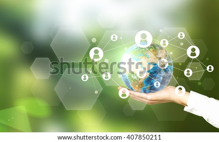 Terrestrial globe with networking system in male palm on abstract green background. Elements of this image furnished by NASA - stock photo