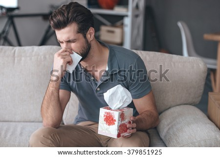 Terrible allergy. Frustrated handsome young man sneezing and using tissue while sitting on the couch at home - stock photo