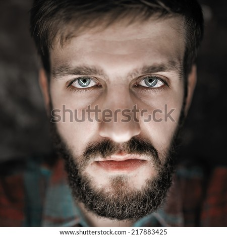 Terrible, angry close-up portrait of a man with a beard - stock photo