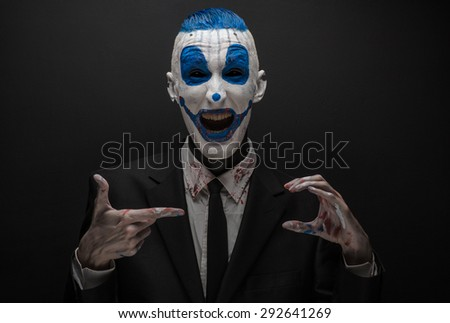 Terrible clown and Halloween theme: Blue Crazy clown in black suit isolated on a dark background in the studio - stock photo