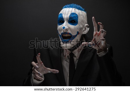 Terrible clown and Halloween theme: Blue Crazy clown in black suit isolated on a dark background in the studio
