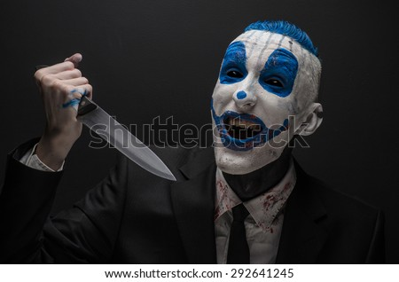 Terrible clown and Halloween theme: Crazy blue clown in a black suit with a knife in his hand isolated on a dark background in the studio - stock photo