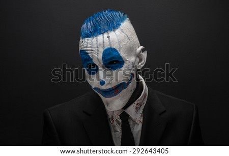 Terrible clown and Halloween theme: Crazy blue clown in black suit isolated on a dark background in the studio - stock photo