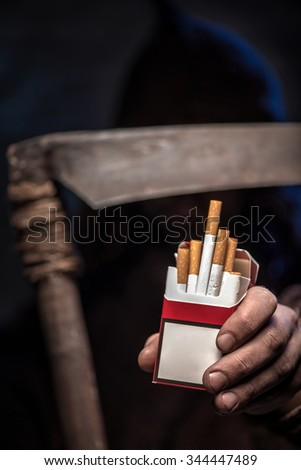 Terrible death is proposing the pack of cigarettes to the camera. He is standing and covering his face with a scythe - stock photo