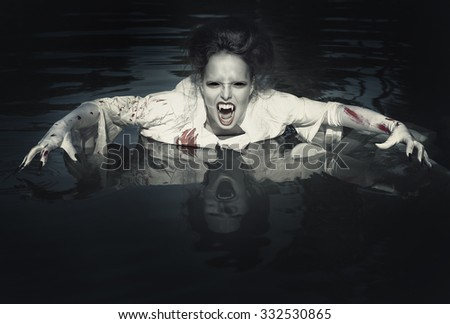 Terrible demon in the bloody shirt standing in the river - stock photo