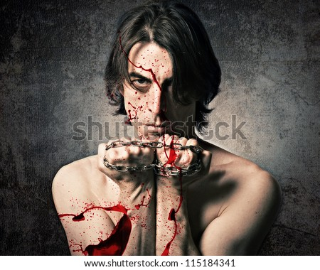 Terrible evil man with an iron chain and covered in blood. - stock photo