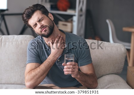 Terrible pain in his throat. Frustrated handsome young man touching his neck and holding a glass of water while sitting on the couch at home - stock photo