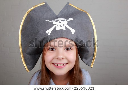 Terrible pirate girl in shirt and hat on a gray background - stock photo