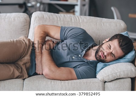 Terrible stomachache. Frustrated handsome young man hugging his belly and keeping eyes closed while lying on the couch at home - stock photo