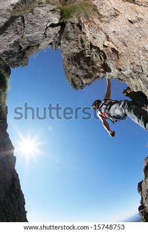 Terrific view of a climbing route: young man climbing a rocky ridge, back-light, fish-eye lens, vertical frame. - stock photo