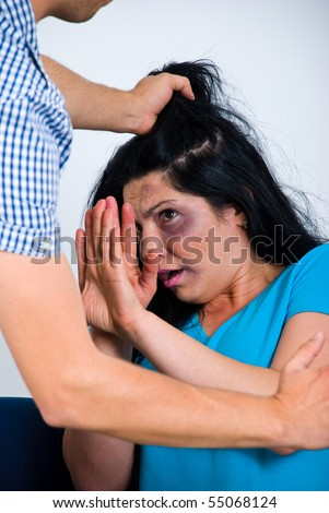 Terrified abused woman trying to stop the attack and defend herself, - stock photo