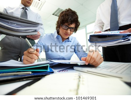 Terrified accountant doing financial reports being surrounded by businessmen with huge piles of documents - stock photo