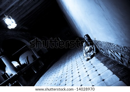 Terrified alone woman on dark corridor - stock photo