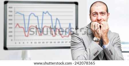 Terrified businessman due to company graphs dropping down - stock photo