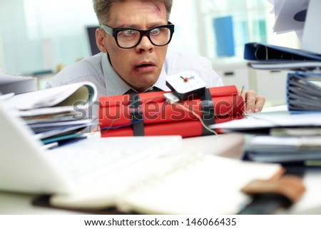 Terrified businessman looking at dynamite in office