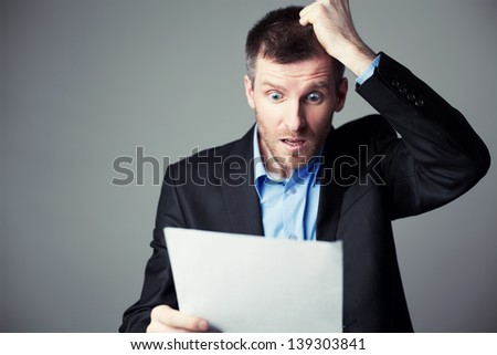 terrified businessman reads contract and pulls his hair from head - stock photo