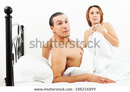 Terrified couple caught during sex in bed - stock photo
