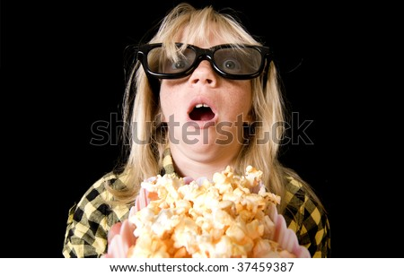 Terrified Girl Wearing New Style 3-D Glasses in a Movie Theater - stock photo
