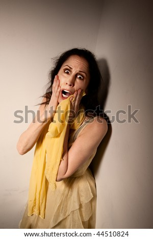 Terrified horror movie style woman trapped in a corner - stock photo