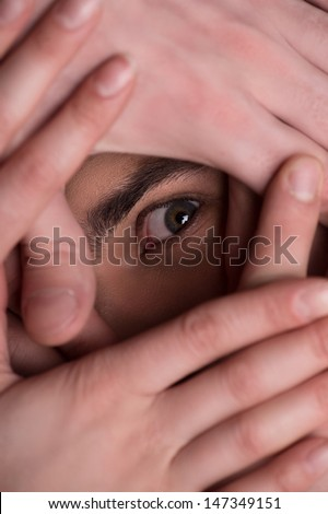 Terrified look. Close-up of human eye looking through the human hands covering face - stock photo