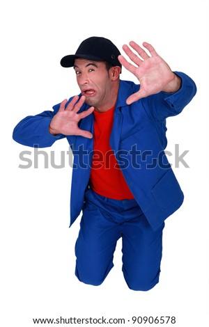 Terrified man kneeling on the floor - stock photo