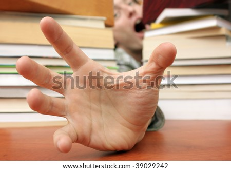 Terrified student needing help (focus on foreground hand) - stock photo