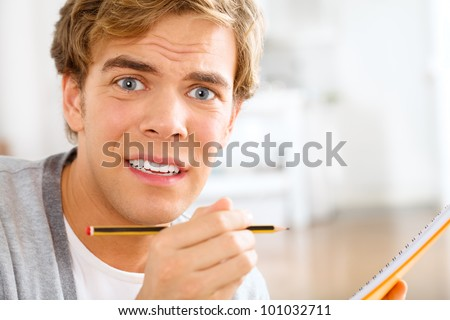 terrified student scared of exams studying at home holding penci - stock photo