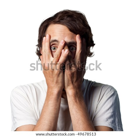 Terrified young man hides his face - stock photo