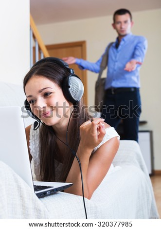 Terrified young man watching girlfriend playing online again - stock photo