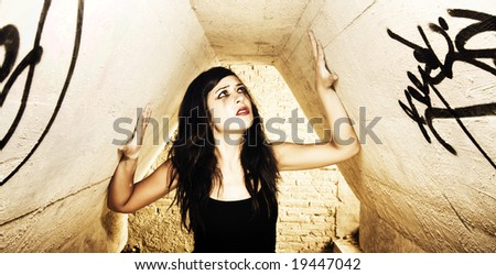 Terrified young woman inside of dirty place. - stock photo