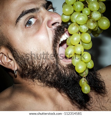 terrifying man with beard who eats voraciously grapes