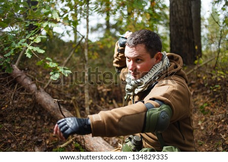 Terrorist at forest throwing knife. - stock photo