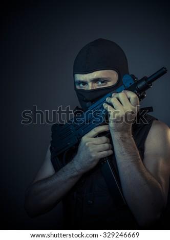 terrorist carrying a machine gun and balaclava - stock photo