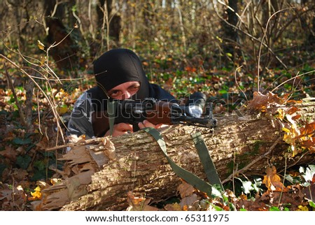 terrorist in camouflage aiming with his rifle outdoor in forest