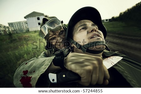 Terrorist is catching a soldier as a hostage. Cross processing styled. Focus point on the soldiers face - stock photo