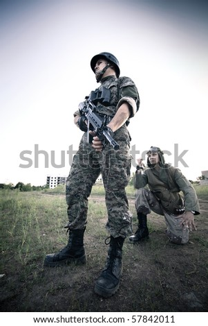Terrorist is catching a soldier as a hostage. Ruined city on the background. Cross processing styled. - stock photo