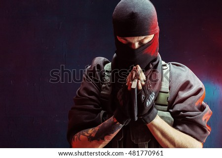 Terrorist praying with a book in his hands
