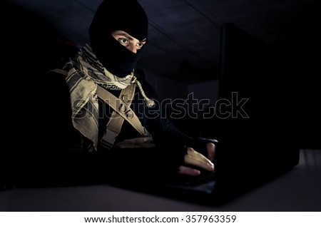 Terrorist working on his computer. Concept about international crisis, war and terrorism - stock photo