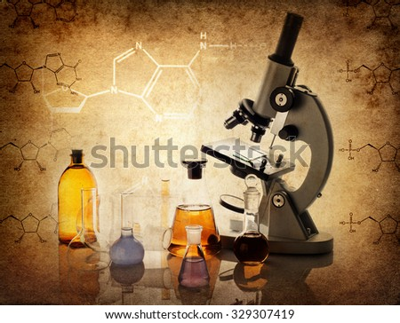 Test glass flask with solution and microscope in research laboratory. Science and medical background. Focus in the foreground. - stock photo
